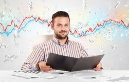 Hombre de negocios que se sienta en la tabla con el gráfico del mercado de acción Imagenes de archivo