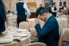 Hombre de negocios que se sienta en la tabla en el banquete usando el teléfono móvil desconciertan al hombre Imagen de archivo libre de regalías
