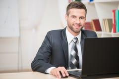 Hombre de negocios que se sienta en la tabla y que trabaja con Fotos de archivo libres de regalías