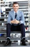 Hombre de negocios que se sienta en las escaleras de la oficina moderna Fotografía de archivo libre de regalías
