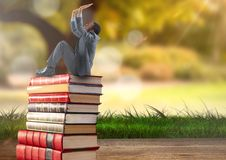 Hombre de negocios que se sienta en los libros apilados por la naturaleza del verdor Imágenes de archivo libres de regalías