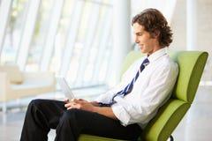Hombre de negocios que se sienta en oficina moderna usando la tablilla de Digitaces Fotos de archivo libres de regalías
