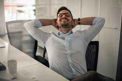 Hombre de negocios que se sienta en oficina y estirado Havin del hombre de negocios imagenes de archivo