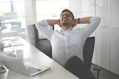Hombre de negocios que se sienta en oficina y estirado Havin del hombre de negocios imagen de archivo libre de regalías