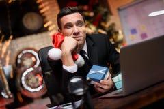 Hombre de negocios que se sienta en oficina y que trabaja en el ` s Eve del Año Nuevo Él está considerando entusiasta el regalo d Imagen de archivo libre de regalías
