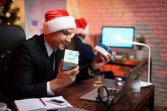 Hombre de negocios que se sienta en oficina y que trabaja en el ` s Eve del Año Nuevo Él está considerando entusiasta el regalo d Fotos de archivo