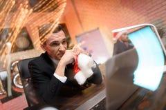 Hombre de negocios que se sienta en oficina y que trabaja en el ` s Eve del Año Nuevo Él mira cuidadosamente a un lado y sostiene Fotos de archivo