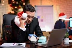 Hombre de negocios que se sienta en oficina y que trabaja en el ` s Eve del Año Nuevo Él mira cuidadosamente a un lado y sostiene Imágenes de archivo libres de regalías
