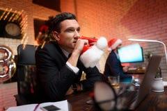 Hombre de negocios que se sienta en oficina y que trabaja en el ` s Eve del Año Nuevo Él mira cuidadosamente a un lado y sostiene Imagenes de archivo