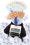 Hombre de negocios que se sienta en piso y que muestra el dinero Imagen de archivo libre de regalías