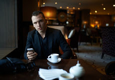 Hombre de negocios que se sienta en restaurante foto de archivo