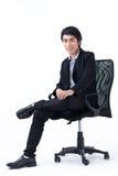 Hombre de negocios que se sienta en silla imagenes de archivo