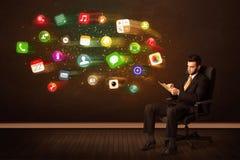 Hombre de negocios que se sienta en silla de la oficina con la tableta y el ap colorido Foto de archivo