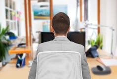Hombre de negocios que se sienta en silla de la oficina de la parte posterior imagen de archivo libre de regalías