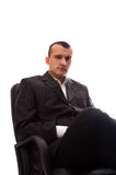 Hombre de negocios que se sienta en silla negra de la oficina Fotografía de archivo libre de regalías