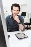 Hombre de negocios que se sienta en su escritorio Foto de archivo