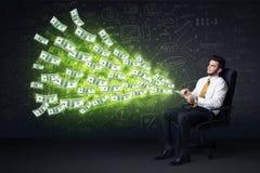 Hombre de negocios que se sienta en tableta de la tenencia de la silla con los billetes de dólar co Foto de archivo