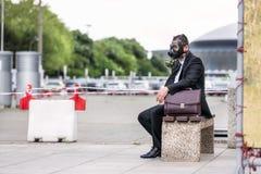 Hombre de negocios que se sienta en un banch con la cartera que lleva una careta antigás en cara Imagenes de archivo