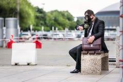 Hombre de negocios que se sienta en un banch con la cartera que lleva una careta antigás que mira al reloj Imagen de archivo libre de regalías