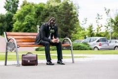 Hombre de negocios que se sienta en un banch que lleva una careta antigás con el teléfono a disposición Fotos de archivo libres de regalías