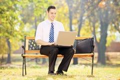 Hombre de negocios que se sienta en un banco y que trabaja en un ordenador portátil en un parque Foto de archivo libre de regalías