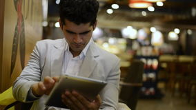 Hombre de negocios que se sienta en un café y que usa una tableta digital almacen de metraje de vídeo