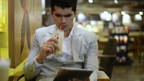 Hombre de negocios que se sienta en un café y que usa una tableta digital metrajes