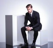Hombre de negocios que se sienta en un cubo que mantiene su mano unida, Imágenes de archivo libres de regalías