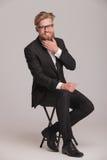 Hombre de negocios que se sienta en un taburete mientras que fija su barba Fotografía de archivo libre de regalías