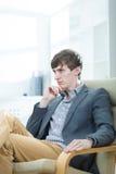 Hombre de negocios que se sienta en una butaca Imagen de archivo