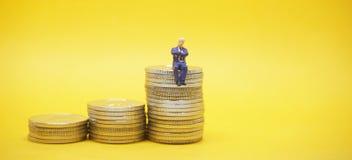 Hombre de negocios que se sienta en una pila de monedas de plata fotografía de archivo