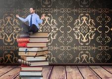 Hombre de negocios que se sienta reflexionando sobre los libros apilados por la antigüedad decorativa del papel pintado Fotografía de archivo