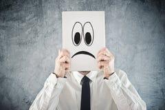Hombre de negocios que se sostiene de papel con la cara triste delante de su cabeza Imagen de archivo