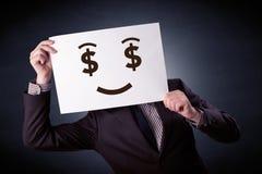 Hombre de negocios que se sostiene de papel con la emoción codiciosa Imagenes de archivo