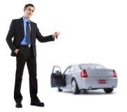 Hombre de negocios que se sostiene dominante a un coche imagen de archivo libre de regalías