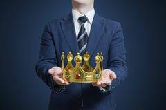 Hombre de negocios que se sostiene en las manos de la corona fotos de archivo