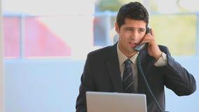 Hombre de negocios que se viste en un traje de negocios que habla en el teléfono almacen de metraje de vídeo