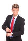 Hombre de negocios que señala impacientemente a su watc Imagenes de archivo