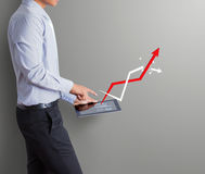 Hombre de negocios que señala la tableta con el aumento de gráfico de la flecha Imágenes de archivo libres de regalías