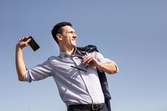 Hombre de negocios que siente enojado mientras que lanza su teléfono lejos fotografía de archivo