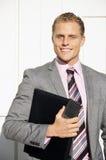 Hombre de negocios que sonríe con la carpeta Fotos de archivo