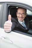 Hombre de negocios que sonríe en la cámara que muestra los pulgares para arriba Fotos de archivo libres de regalías