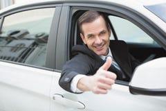 Hombre de negocios que sonríe en la cámara que muestra los pulgares para arriba Fotos de archivo