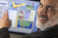 Hombre de negocios que sonríe y que señala al ordenador Monit Imagenes de archivo