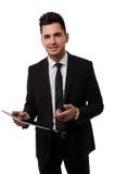 Hombre de negocios que sonríe y que señala en una tableta Fotos de archivo libres de regalías