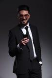 Hombre de negocios que sonríe mientras que sostiene un teléfono Fotos de archivo libres de regalías