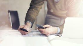 Hombre de negocios que sostiene businesscard de la mano y que hace smartphone de la foto Proyecto arquitectónico sobre la tabla m Foto de archivo libre de regalías