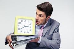 Hombre de negocios que sostiene carpetas y que mira en el reloj Fotos de archivo libres de regalías