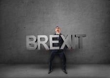 Hombre de negocios que sostiene 3d y x27 pesados; brexit& x27; palabra en sus manos Imagenes de archivo