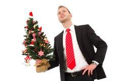 Hombre de negocios que sostiene el árbol de navidad - hombre aislado en la parte posterior del blanco Fotos de archivo